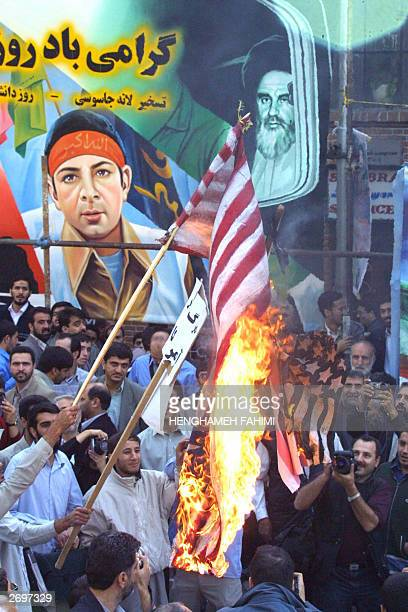 Iranian demonstrators burn the US flag in front of the former US embassy in Tehran 04 November 2003 Some 10000 Iranian hardliners gathered outside...
