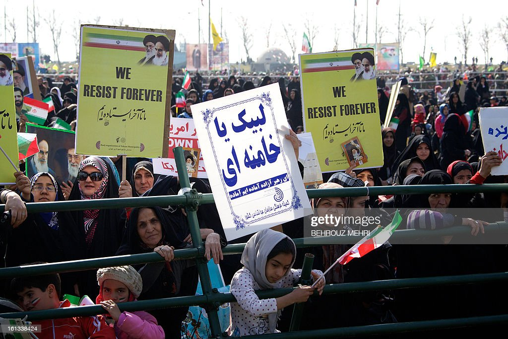 Iranian demonstrators hold placards during a rally in Tehran's Azadi Square (Freedom Square) to mark the 34th anniversary of the Islamic revolution on February 10, 2013. Hundreds of thousands of people marched in Tehran and other cities chanting 'Death to America' and 'Death to Israel' as Iran celebrated the anniversary of the ousting of the US-backed shah.