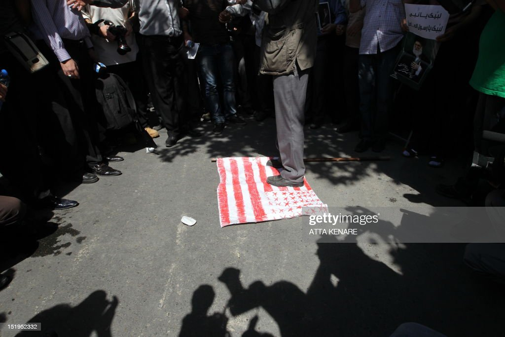 Iranian demonstrators step on the US flag during a protest against a film mocking Islam, on September 13, 2012 near the Swiss embassy in Tehran . Up to 500 people protested in Tehran over the anti-Islam film made in the United States, chanting 'Death to America!' and death to the movie's director. The rally, near the Swiss embassy that handles US interests in the absence of US-Iran diplomatic ties, ended peacefully two hours later.