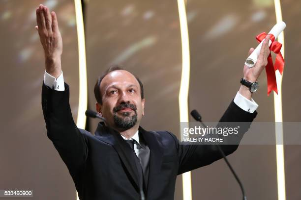 TOPSHOT Iranian director Asghar Farhadi celebrates on stage after being awarded with the Best Screenplay prize for the film 'The Salesman during the...
