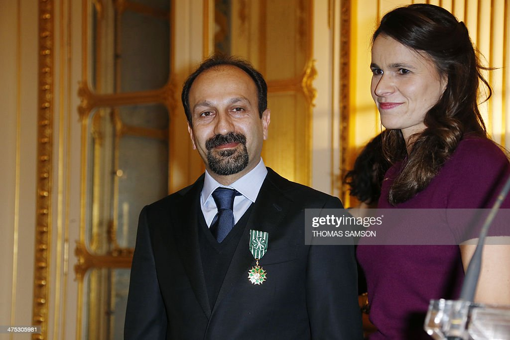 Iranian director Asghar Farhadi (L) poses for a photograph alongside French Minister of Culture Aurelie Filippetti after being awarded an 'Officier des Arts et Lettres' medal by the French Minister of Culture, in Paris, on February 27, 2014. Farhadi, who directed the Oscar-winning Iranian film 'A separation' and whose latest film 'The Past' is nominated for the upcoming Academy Awards in March, received the French arts and culture award from the hands of the French Minister of Culture. AFP PHOTO / THOMAS SAMSON