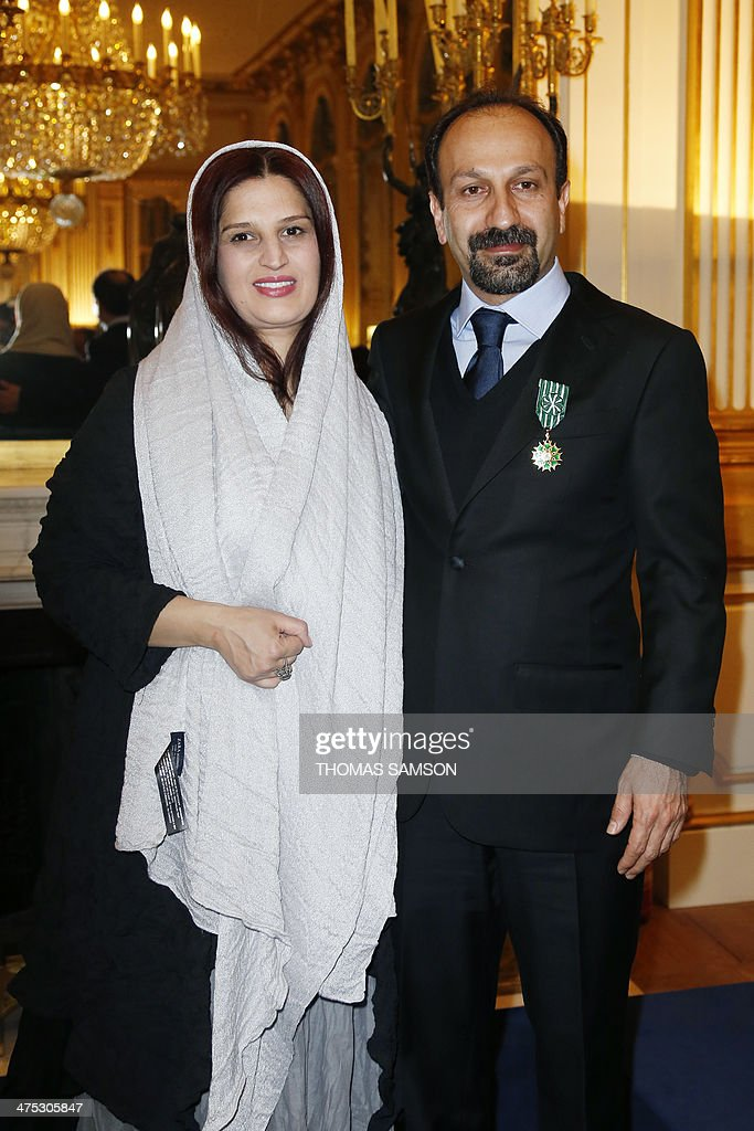 Iranian director Asghar Farhadi poses for a photograph with his wife Parisa after being awarded an 'Officier des Arts et Lettres' medal by the French Minister of Culture, in Paris, on February 27, 2014. Farhadi, who directed the Oscar-winning Iranian film 'A separation' and whose latest film 'The Past' is nominated for the upcoming Academy Awards in March, received the French arts and culture award from the hands of the French Minister of Culture. AFP PHOTO / THOMAS SAMSON