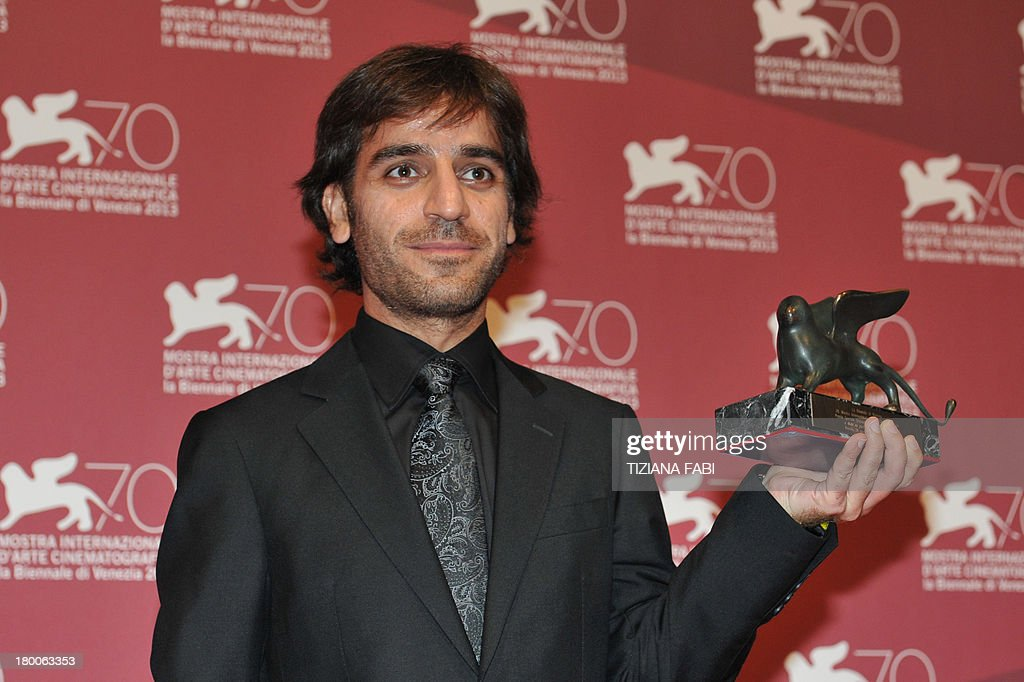 Iranian director Shahram Mokri poses with the Special Orizzonti award for Innovative Content he received for his movie 'Mahi Va Gorbeh' (Fish Cat) during a photocall at the award ceremony of the 70th Venice Film Festival on September 7, 2013 at Venice Lido.