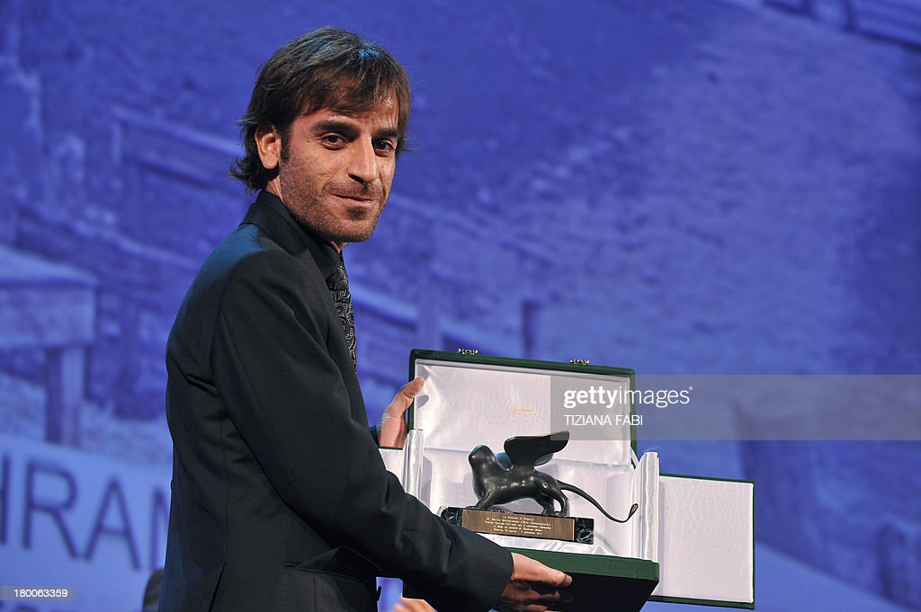 Iranian director Shahram Mokri poses with the Special Orizzonti award for Innovative Content he received for his movie 'Mahi Va Gorbeh' (Fish Cat) during the award ceremony of the 70th Venice Film Festival on September 7, 2013 at Venice Lido.