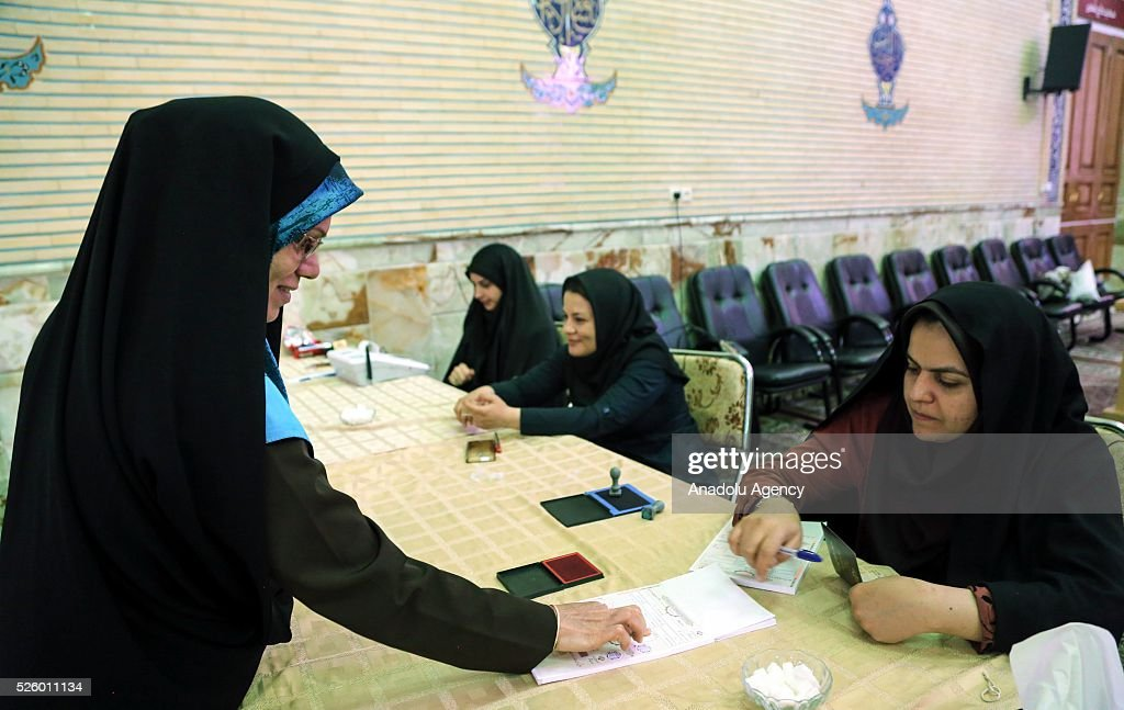 Iranian election official checks identities during a second round of parliamentary elections at a polling station in Shahriar district of Tehran, Iran on April 29, 2016.