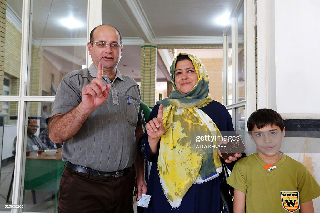 Iranian family members display their ink-stained fingers after casting their ballot to vote in the second round of parliamentary elections at a polling station in the town of Robat Karim, some 40 kms southwest of the capital Tehran, on April 29, 2016. Iranians started voting in second round elections for almost a quarter of parliament's seats, the latest political showdown between reformists and conservatives seeking to influence the country's future. Polling stations opened at 8:00 am (0330 GMT) for the ballot which is taking place in 21 provinces, but not Tehran, because no candidate in 68 constituencies managed to win 25 percent of votes cast in initial voting on February 26. Reformists who backed moderate President Hassan Rouhani made big gains in the first round following Iran's implementation of a nuclear deal with world powers, which lifted sanctions blamed for long hobbling the economy. Conservative MPs, including vehement opponents of the West who openly criticised the landmark agreement that reined in Iran's atomic programme, lost dozens of seats and were wiped out in Tehran where reformists won all 30 places in parliament. / AFP / ATTA