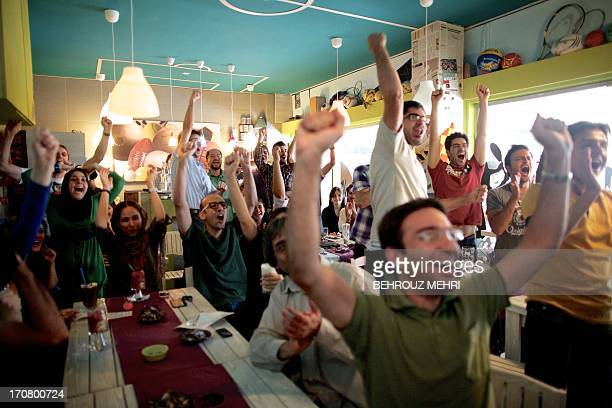 Iranian fans celebrate in a cafe after their national team scored the only goal of the 2014 World Cup Asian zone group A qualifying football match...