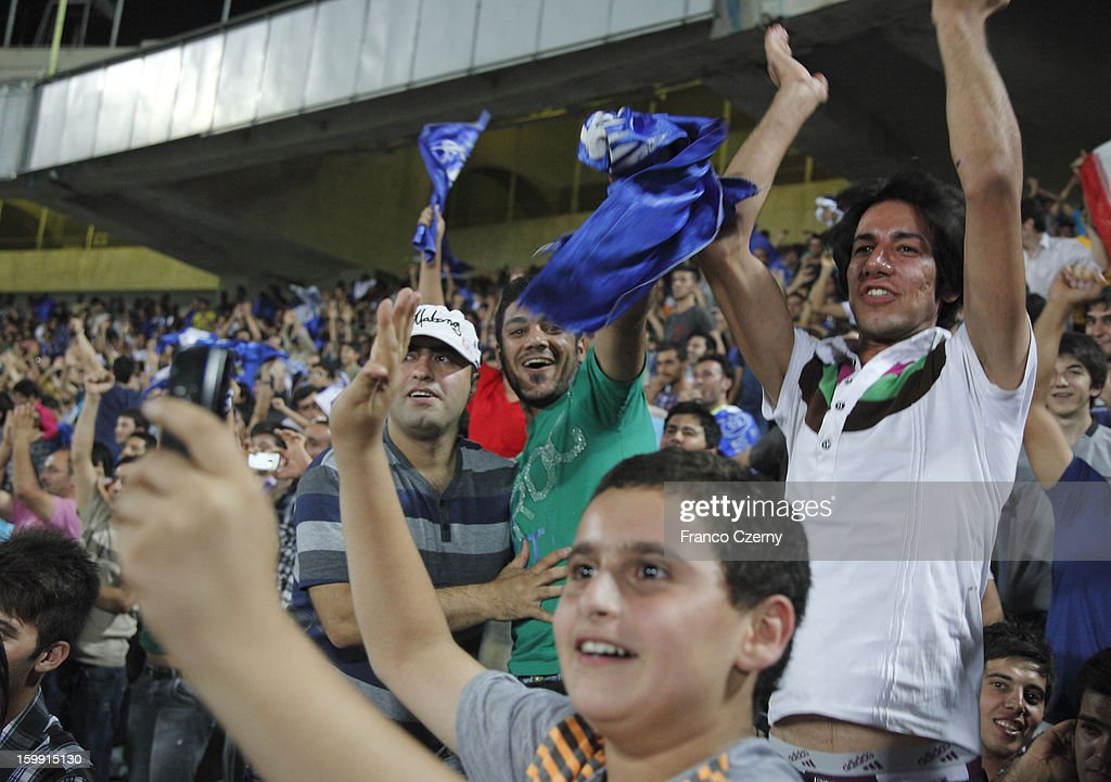 Iranian fans of Esteghlal football club celebrate a goal during a match at the Azadi Sports Complex on August 19, 2012 in Tehran, Iran.