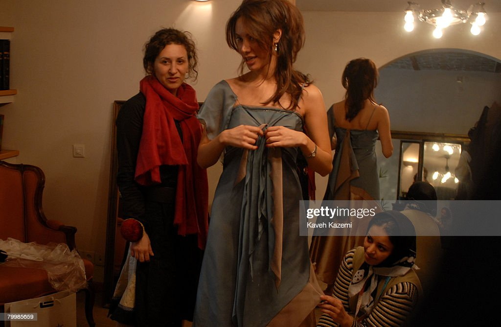 Iranian fashion designer Shadi Parand (left) watches a dress being fitted for a client, Tehran, 10th March 2007.
