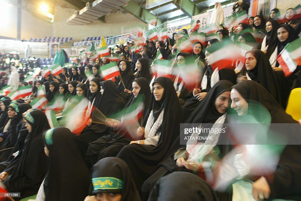 Iranian female students members of the hardline Basij Islamic militia wave small Iranian flags during a gathering on the occasion of Student Basij...