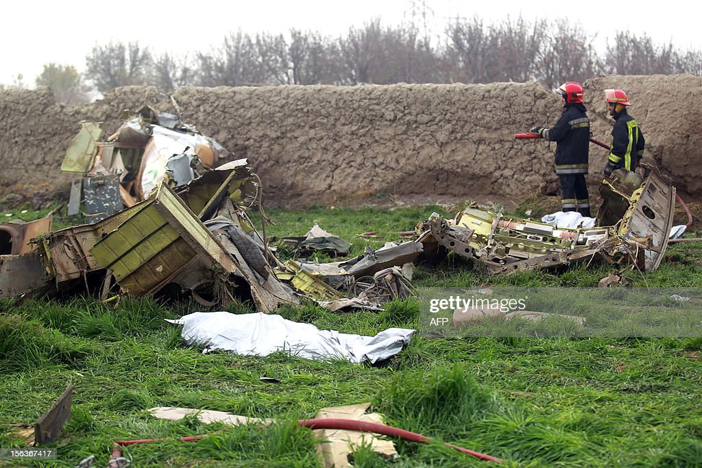 Iranian fire fighters look at the debris on a helicopter that crashed on November 14, 2012, close to Mashhad. Ten people were killed when the rescue helicopter ferrying wounded people from a vehicle accident to hospital hit power lines and crashed to the ground in northeastern Iran, media reported.