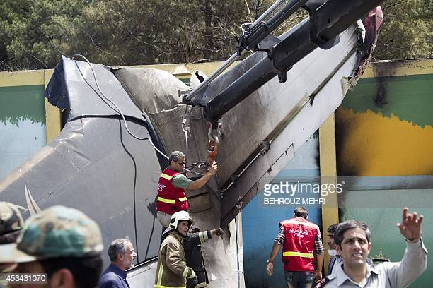 Iranian firemen attach the remains of a plane to a crane to remove it from the scene of a crash near Tehran's Mehrabad airport on August 10 2014 An...