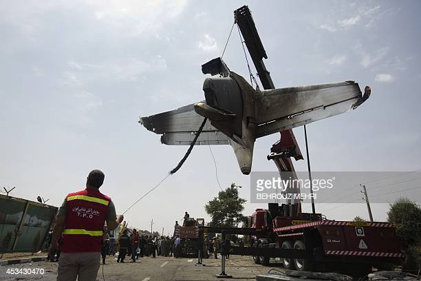 Iranian firemen relocate the remains of a plane as they secure the scene of a crash near Tehran's Mehrabad airport on August 10 2014 An Iranian...