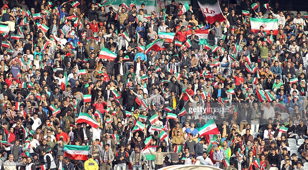 Iranian football fans cheer for their team during their 2015 AFC Asian Cup group B qualifying football match against Lebanon at the Azadi Stadium in Tehran on February 6, 2013. Iran won the match 5-0.