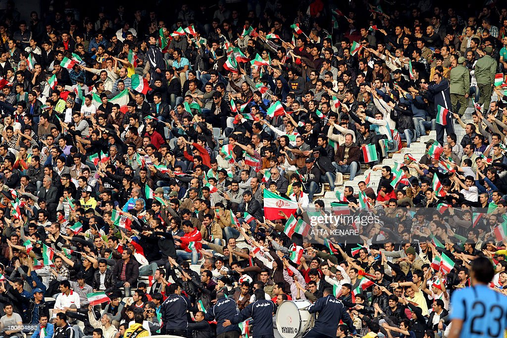 Iranian football fans cheer for their team during their 2015 AFC Asian Cup group B qualifying football match against Lebanon at the Azadi Stadium in Tehran, on February 6, 2013. Iran won the match 5-0.