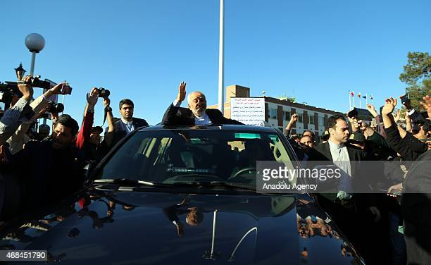 Iranian Foreign Minister Mohammad Javad Zarif greets people as nuclear negotiating committee arrive at Mehrabat Airport in Tehran on April 3 after...