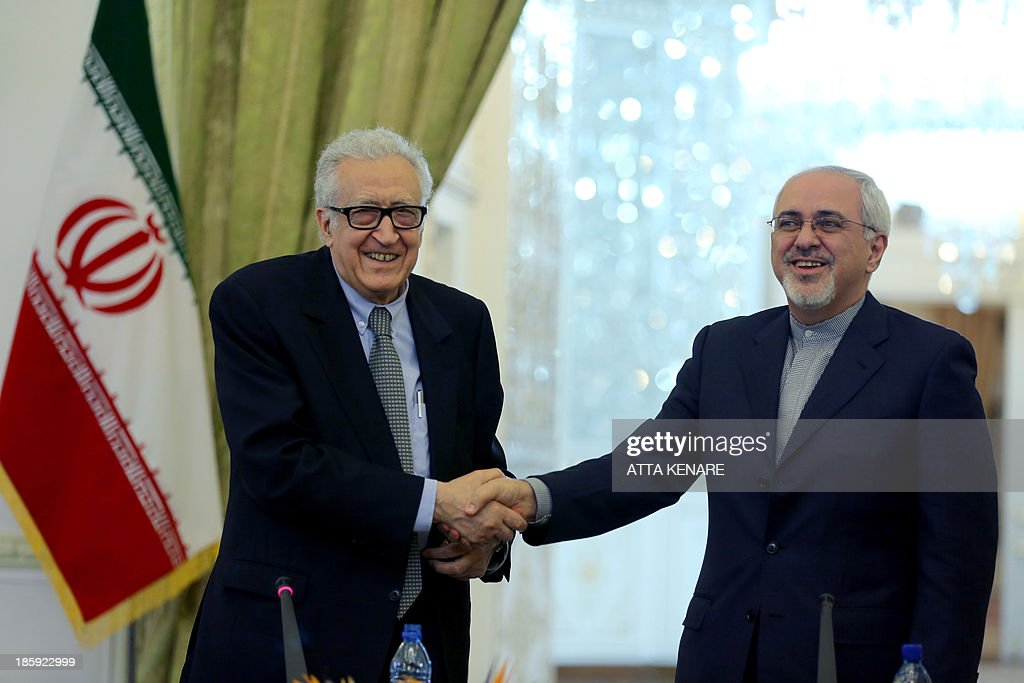 Iranian Foreign Minister Mohammad Javad Zarif (R) shakes hands with International Peace envoy to Syria Lakhdar Brahimi during a joint press conference in Tehran on October 26, 2013. The UN-Arab League envoy to war-torn Syria said Iran's participation in international peace talks on the conflict was 'necessary,' Mehr news agency reported.