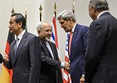 Iranian Foreign Minister Mohammad Javad Zarif shakes hands with US Secretary of State John Kerry next to Chinese Foreign Minister Wang Yi and French...