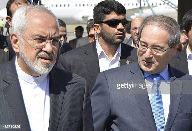 Iranian Foreign Minister Mohammad Javad Zarif walks alongside Syria's deputy foreign minister Faisal Muqdad upon his arrival Damascus international...