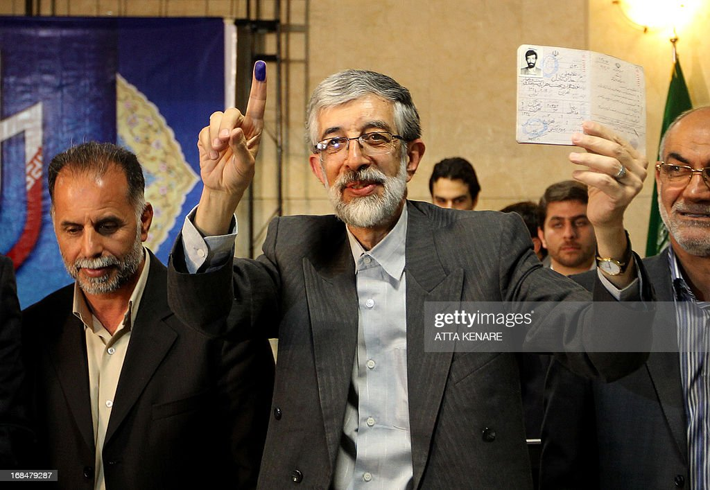 Iranian former parliament speaker Gholam Ali Haddad Adel holds up his ID after registering his candidacy for the upcoming presidential election at the interior ministry in Tehran on May 10, 2013. Iran began a five-day registration period for candidates in Iran's June 14 presidential election, with a string of conservative hopefuls in the running but with key reformists yet to come forward, media reports said.