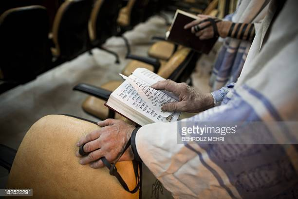 Iranian Jewish men read from the Torah during morning prayers at Youssef Abad synagogue in Tehran on September 30 2013 Present for more than 2500...