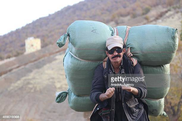 Iranian Kurdish border smuggler who was handicapped after stepping on land mines carries goods mostly consisting of electronic devices and white...
