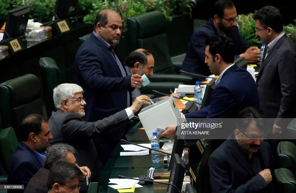 Iranian leading reformist MP, Mohammad Reza Aref (C-L) casts his vote for the new Parliament speaker, during a parliament in Tehran on May 29, 2016. / AFP / ATTA