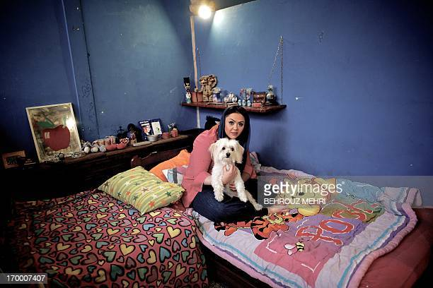 Iranian Media poses for a picture with her Terrier dog Shiny in her bedroom in Tehran on May 28 2013 For decades pet dogs were rare and thus...