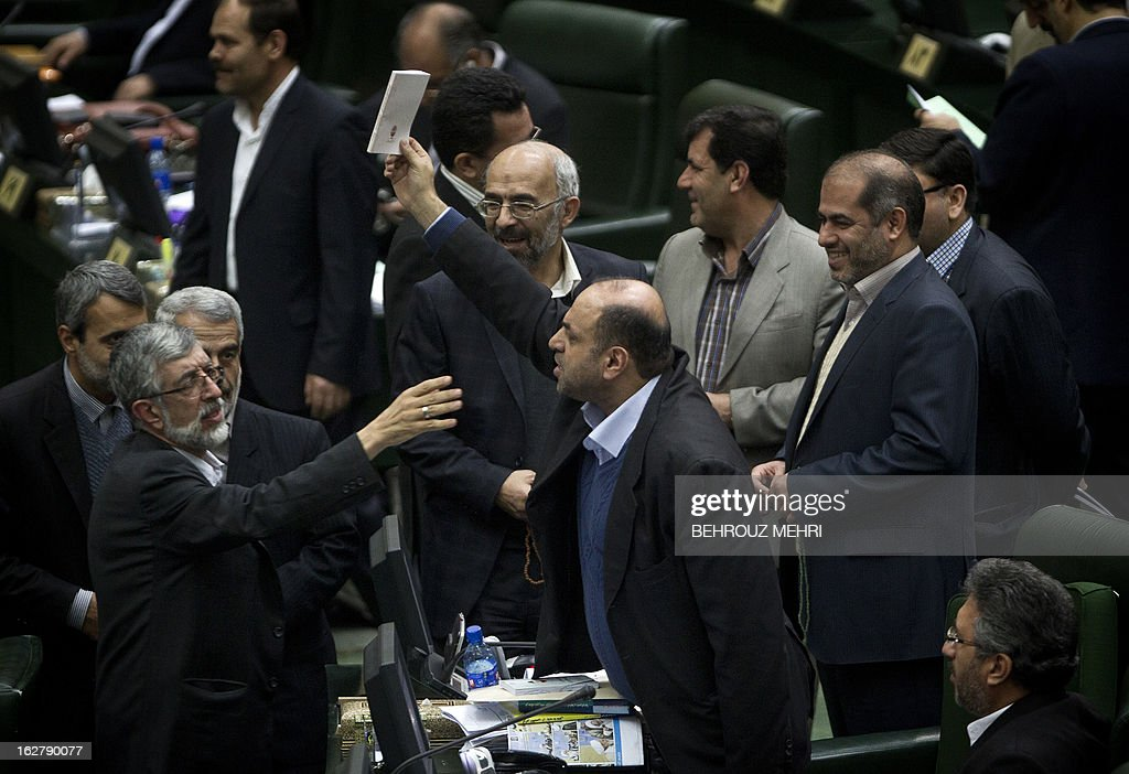 Iranian member of parliament (MP) Gholam Ali Haddad Adel (L) tries to calm MP Iraj Nadimi (C) while discussing a draft to limit photographer's and cameramen's access to cover parliament's open sessions in Tehran on February 27, 2013. The debate took part on the sidelines of a parliamentary session to discuss the annual budget bill which is being presented by the government.