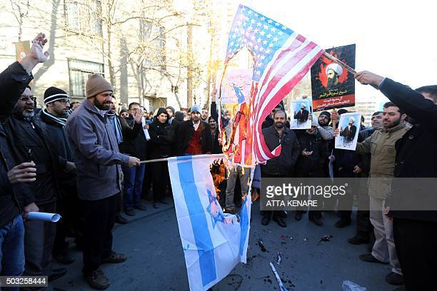 Iranian men burn Israeli and American flags during a demonstration against the execution of prominent Shiite Muslim cleric Nimr alNimr by Saudi...