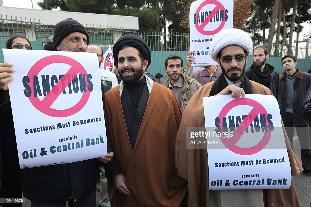 Iranian men hold placards during a demonstration outside the Tehran Research Reactor in the capital Tehran on November 23 to show their support to...