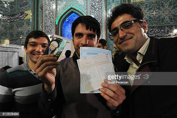 Iranian men hold up ballot marked with reformist candidates and as they vote in key elections for Parliament and the Assembly of Experts in the...