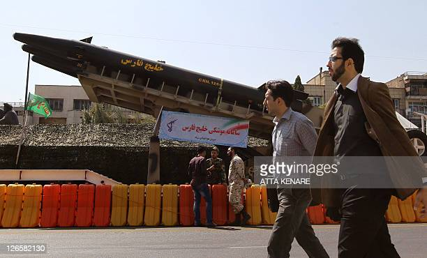 Iranian men walk past a longrange 'Khalij Fars ' antiship ballistic missile displayed at a square in southern Tehran on September 26 2011 to mark the...