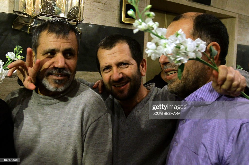 Iranian men who had been held hostage by Syrian rebels since early August celebrate as they arrive at a hotel in Damascus after being freed in a prisoner swap on January 9, 2013. A total of 48 Iranians were released in the unprecedented exchange for 2,130 prisoners detained by President Bashar al-Assad's regime, according to several sources. AFP PHOTO/LOUAI BESHARA