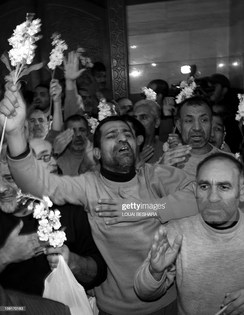 Iranian men who had been held hostage by Syrian rebels since early August celebrate as they arrive at a hotel in Damascus after being freed in a prisoner swap on January 9, 2013. A total of 48 Iranians were released in the unprecedented exchange for 2,130 prisoners detained by President Bashar al-Assad's regime, according to several sources. PHOTO / Louai Beshara