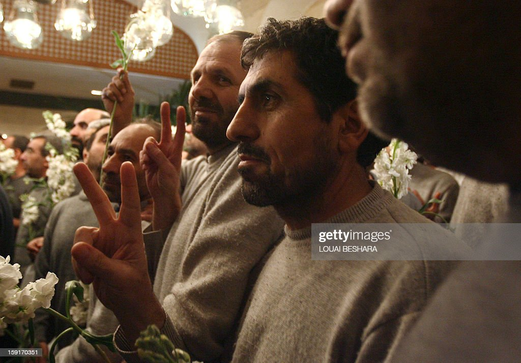Iranian men who had been held hostage by Syrian rebels since early August make victory signs as they arrive at a hotel in Damascus after being freed in a prisoner swap on January 9, 2013. A total of 48 Iranians were released in the unprecedented exchange for 2,130 prisoners detained by President Bashar al-Assad's regime, according to several sources. AFP PHOTO/LOUAI BESHARA