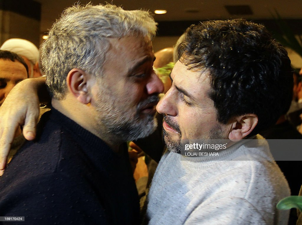 Iranian men who had been held hostage by Syrian rebels since early August congratulate each other as they arrive at a hotel in Damascus after being freed in a prisoner swap on January 9, 2013. A total of 48 Iranians were released in the unprecedented exchange for 2,130 prisoners detained by President Bashar al-Assad's regime, according to several sources. AFP PHOTO/LOUAI BESHARA