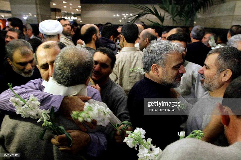 Iranian men who had been held hostage by Syrian rebels since early August congratulate each other as they arrive at a hotel in Damascus after being freed in a prisoner swap on January 9, 2013. A total of 48 Iranians were released in the unprecedented exchange for 2,130 prisoners detained by President Bashar al-Assad's regime, according to several sources.