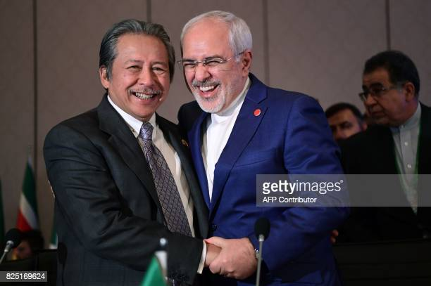 Iranian Minister of Foreign Affairs Mohammad Javad Zarif and Malaysian foreign minister Dato Sri Anifah Aman shake hands as they attend the Executive...