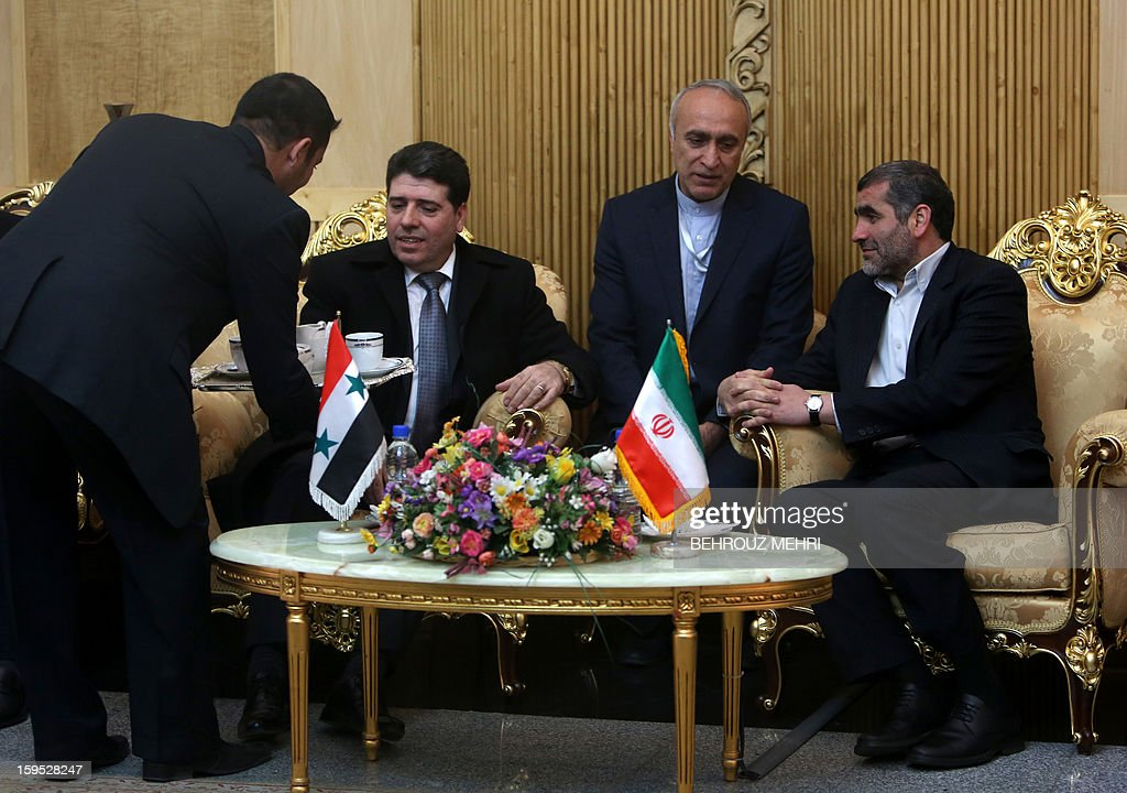 Iranian Minister of Roads and Urban Developments Ali Nikzad (R) greets Syrian Prime Minister Wael al-Halaqi (L) upon his arrival at Tehran's Mehrabad airport on January 15, 2013, a week after Syrian rebels freed 48 Iranians held hostage for more than five months.