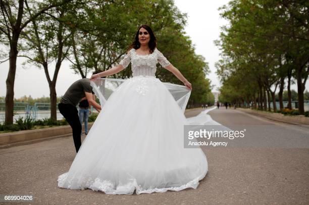 Iranian model Chunur Muhammed displays the custom made 200 meter long wedding dress at Sami Abdulrahman Park in Erbil Iraq on April 18 2017 Custom...