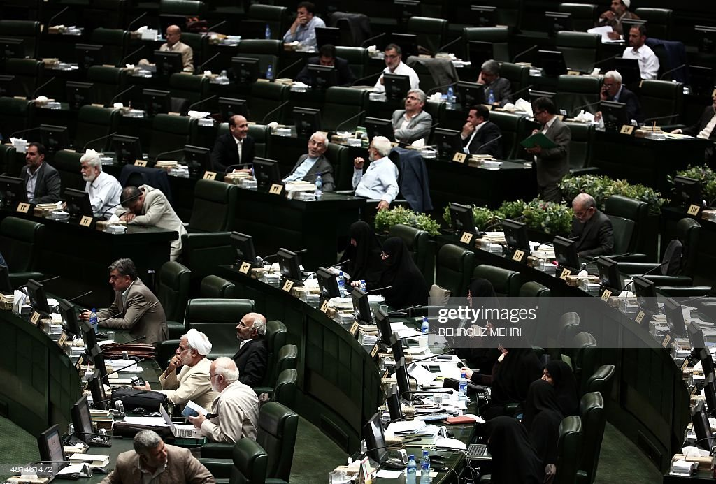 Iranian MPs listen to the speech of Foreign Minister Mohammad Javad Zarif in the parliament in Tehran on July 21 2015 to defend last week's Vienna...