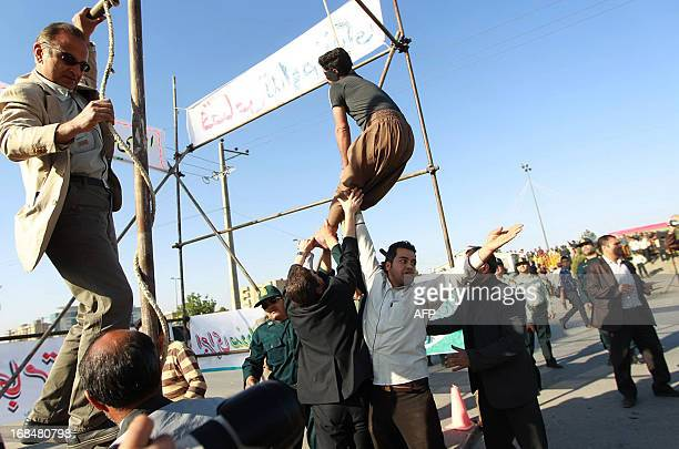 Iranian officials try to save a man with a noose around his neck seconds after his public execution for killing of a policeman in the northeastern...