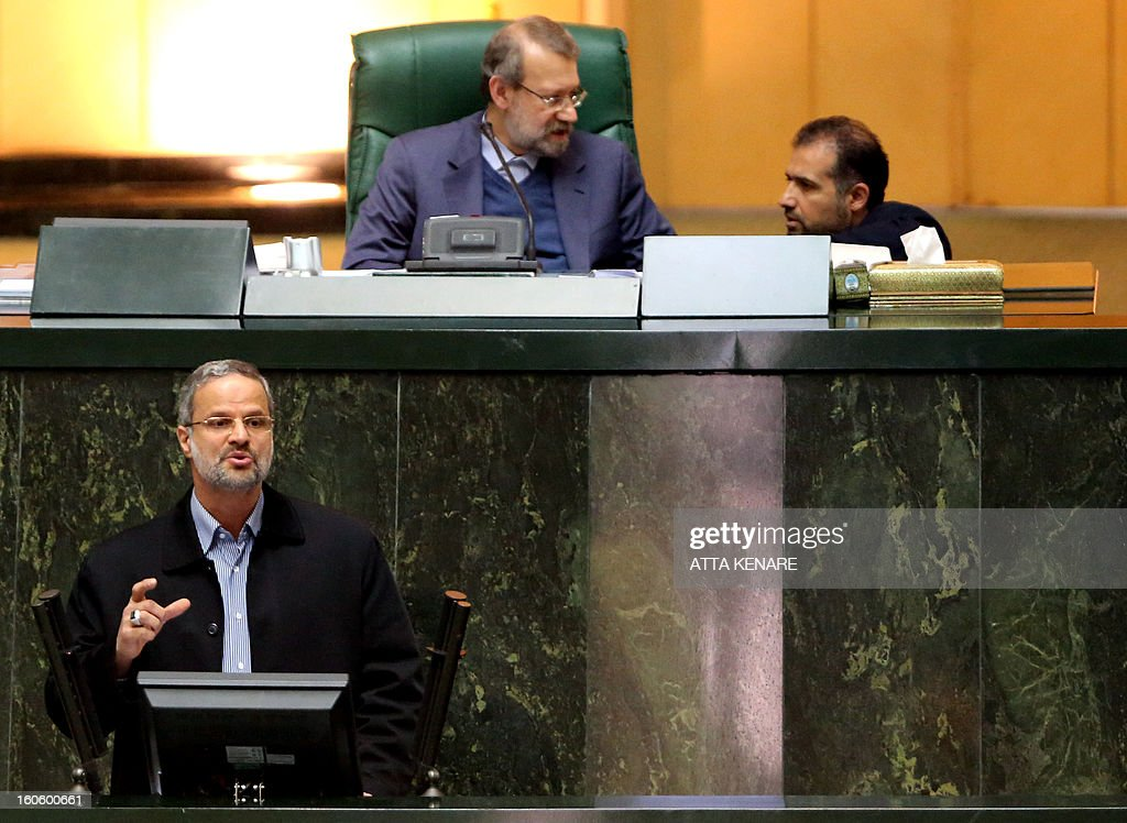 Iranian Parliament Speaker Ali Larijani (top-L) speaks with a politician as Labour and social welfare minister, Abdolreza Sheikholeslam, delivers a speech to the parliament in Tehran on February 3, 2013. A large majority of MPs voted in a heated parliament session, broadcast on state radio, to remove Sheikholeslam for refusing to sack a controversial figure, Saeed Mortazavi.