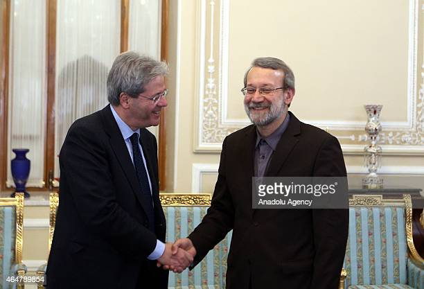 Iranian Parliamentary Speaker Ali Larijani and Italian Foreign Minister Paolo Gentiloni shake hands before a meeting held at the Parliament in Tehran...