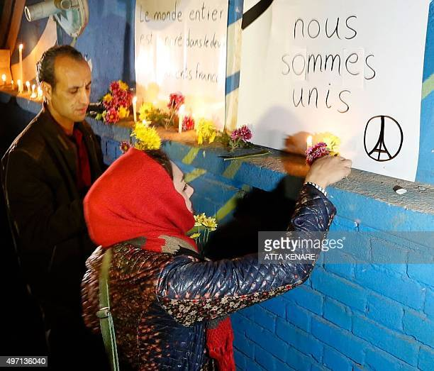 Iranian people pay tribute to the victims of the attacks in Paris outside the French embassy in Tehran on November 14 2015 At least 128 people were...