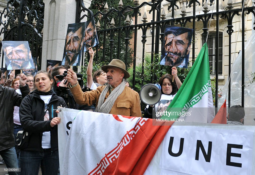 Iranian photographer Reza (C with hat) and Media rights watchdog Reporters Sans Frontieres (Reporters Without Borders - RSF) members hold up crumpled portraits of Iranian President Mahmoud Ahmadinejad during a protest in front of the Iranian embassy in Paris, on May 3, 2010, calling for the release of emprisonned journalists in Iran.