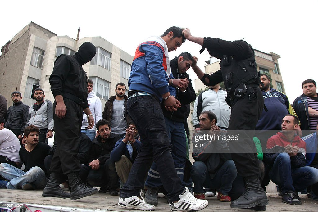 Iranian police round-up men after arresting them in the capital Tehran, on December 25, 2012. Police in Tehran said they had arrested more than 100 'thugs' as part of an operation to curb violent crime after the brutal assault of a man was captured on a surveillance camera.