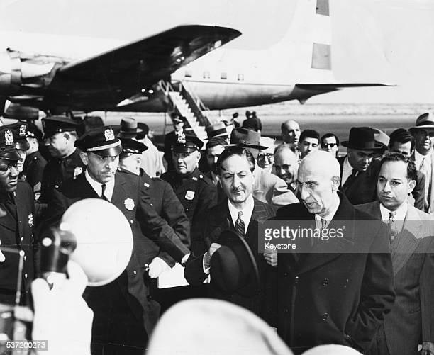 Iranian politician Mohammed Mossadegh surrounded by press and officials as he arrives at an airport circa 1955