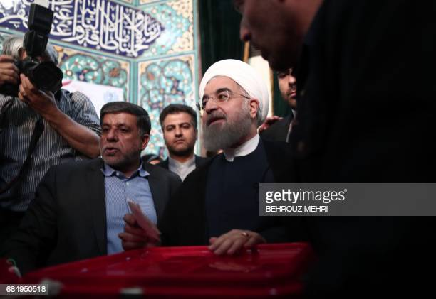 Iranian President and presidential candidate Hassan Rouhani prepares to cast his ballot for the presidential elections at a polling station in Tehran...